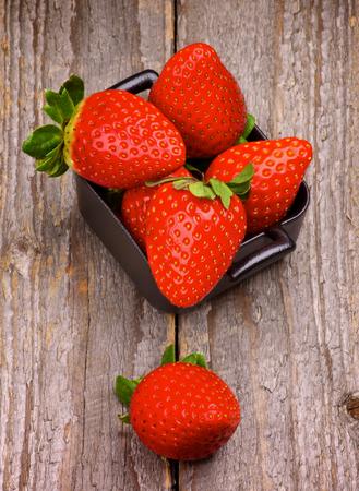 forme carre: Pile de parfaits premi�res fraises de Carr� Noir Bowl isol� sur fond en bois rustique Banque d'images