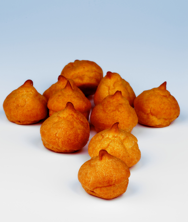 choux bun: Heap of Freshly Baked Profiteroles isolated on Blue background