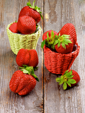 Ripe Strawberries in Colorful Wicker Baskets isolated on Wooden background photo