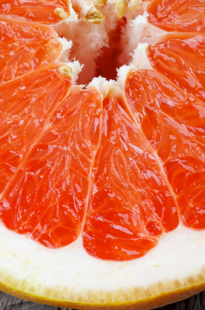 Background of Fresh Juicy Red Grapefruit Slice Cross Section closeup photo