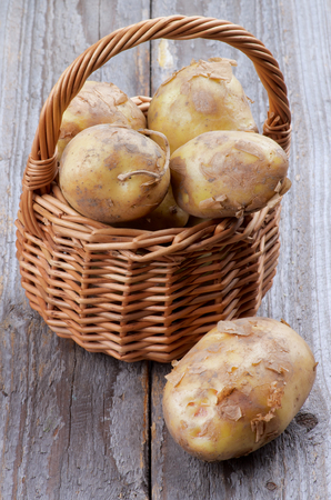 russet potato: New Harvest Potato with Natural Dirties in Wicker Basket isolated on Rustic Wooden background