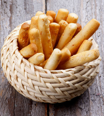 breadstick: Bread Sticks with Sesame Seeds in Wicker Bowl isolated on Rustic Wooden background