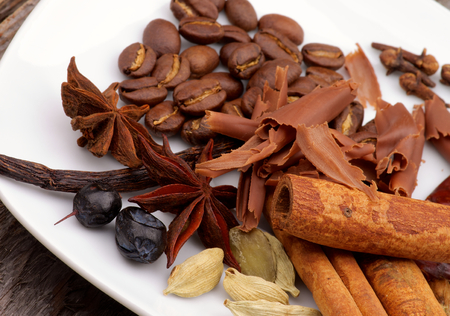 Arrangement of Coffee Beans and Cinnamon Stick with Chocolate Slices, Vanilla Pods, Anise Stars, Cardamon and Barberry on White Plate closeup photo