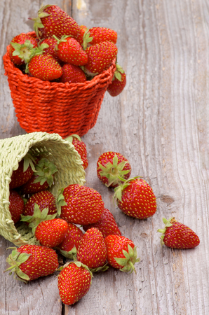 Fresh Ripe Forest Strawberries in Green and Red Wicker Baskets closeup on Rustic Wooden background photo
