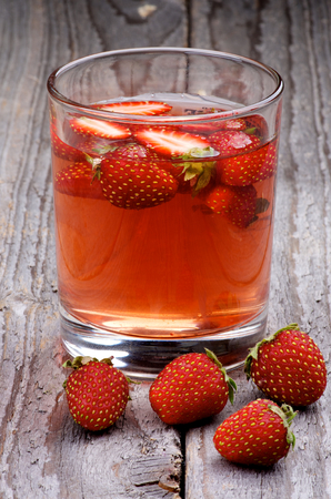 Homemade Strawberry Drink with Fresh Forest Strawberries in Glass on Wooden background photo