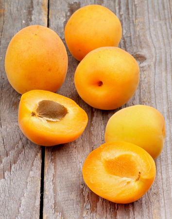 Arrangement of Fresh Juicy Apricots Full Body and Halves isolated on Rustic Wooden background photo