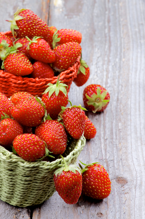 Fresh Ripe Forest Strawberries in Red and Green Wicker Baskets closeup on Rustic Wooden background photo