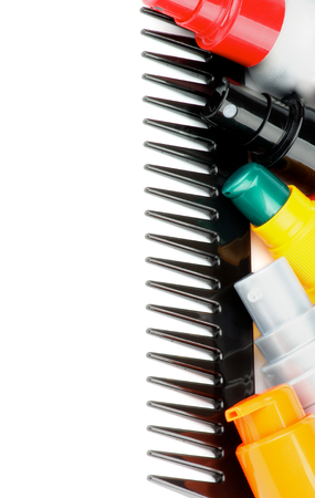 Frame of Colorful Various Hair Styling Products on Black Comb isolated on white background Foto de archivo