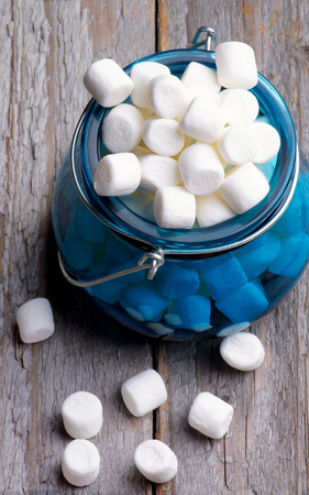 White Vanilla Mini Marshmallow in Blue Glass Jar isolated on Rustic Wooden background photo