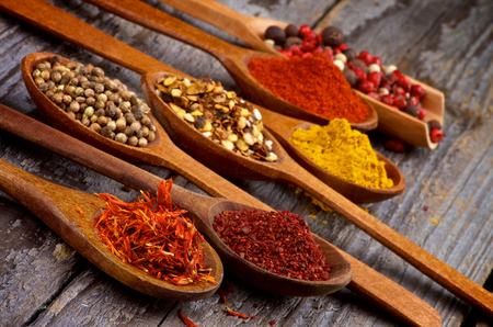 Wooden Spoons with Saffron, Sumac, Coriander, Dried Chili, Curry Powder, Paprika and Mixed Pepper closeup on Rustic Wooden background