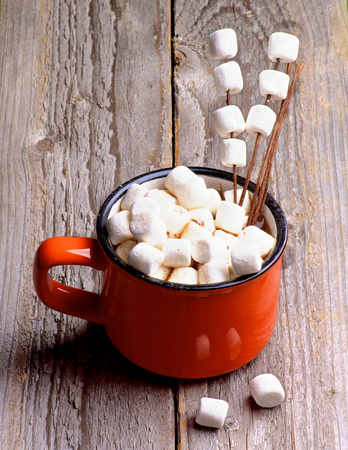 Hot Chocolate in Orange Cup with Marshmallows on Wooden Stems isolated on Rustic Wooden background Foto de archivo