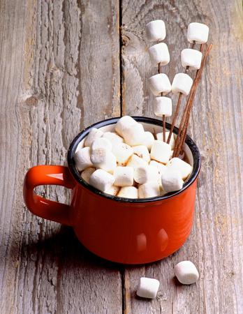 Heiße Schokolade in Orange Cup mit Marshmallows auf hölzernen Vorbauten isoliert auf rustikale hölzerne Hintergrund Lizenzfreie Bilder