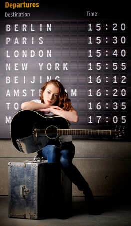 arrival departure board: Attractive Young Woman with Guitar Sitting on Obsolete Suitcase against Arrival  Departure Board Stock Photo