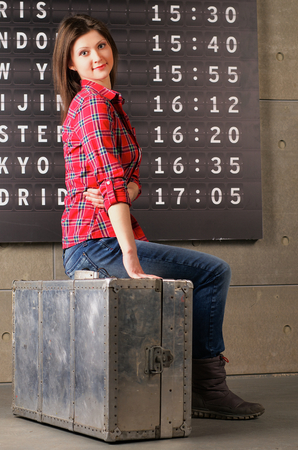 Attractive Young Woman in Checkered Shirt Sitting on Obsolete Suitcase against Arrival Departure Board photo
