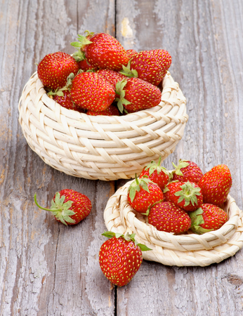 Fresh Ripe Forest Strawberries in Wicker Bowls isolated on Rustic Wooden background photo