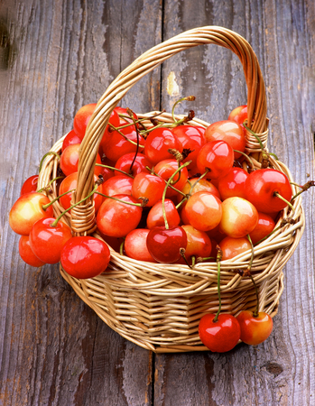 maraschino: Sweet Maraschino Cherries in Wicker Basket on Rustic Wooden background Stock Photo