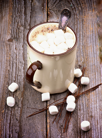 Beige Cup with Hot Chocolate and Vanilla Marshmallows isolated on Rustic Wooden background photo