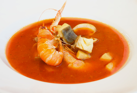 Stewed Bouillabaisse Soup with Delicious Seafood closeup in White Bowl photo