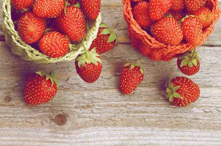 denominado retro: Forest Strawberries in Red and Green Wicker Baskets on Rustic Wooden background  Retro Styled