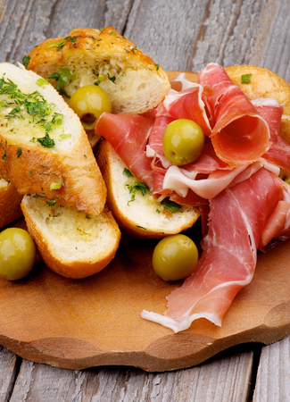 Delicious Tapas with Smoked Jamon, Garlic Bread and Green Olives on Wooden Plate closeup on Wooden background photo