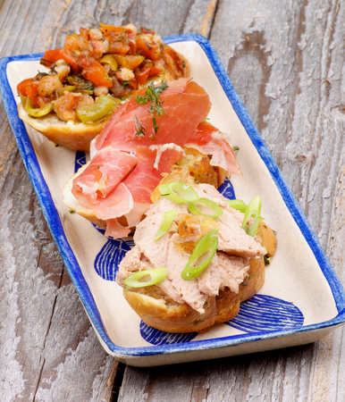 Tapas Bruschetta with Pate with Spring Onion, Cured Ham and Bacon with Vegetables on Garlic Bread on Plate isolated on Rustic Wooden background photo