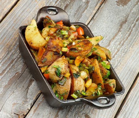 Roasted Potato Wedges with Greens and Paprika in Black Fry Pan isolated on Rustic Wooden background. Stock Photo