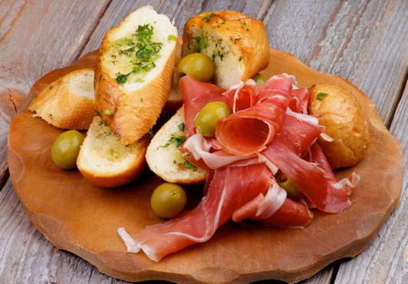 Arrangement of Delicious Tapas with Smoked Jamon, Garlic Bread and Green Olives on Wooden Plate isolated on Rustic Wooden background photo