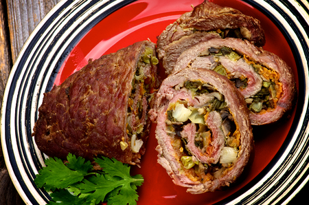 Rolled Beef Meatloaf Stuffed with Leek, Carrot and Greens Half and Slices on Red Plate photo