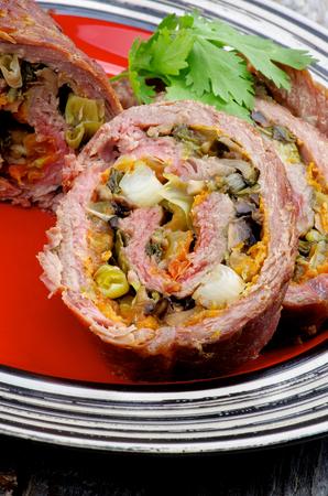 albondigas: Rebanadas de pan con carne de ternera rellenos laminado con puerro, zanahoria y verdes primer plano en la placa roja