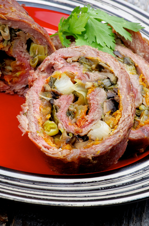 meatloaf: Slices of Rolled Beef Meatloaf Stuffed with Leek, Carrot and Greens closeup on Red Plate Stock Photo