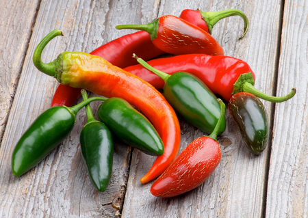 Arrangement of Red and Green Habanero and Jalape?o Chili Peppers isolated on Rustic Wooden background Stock Photo