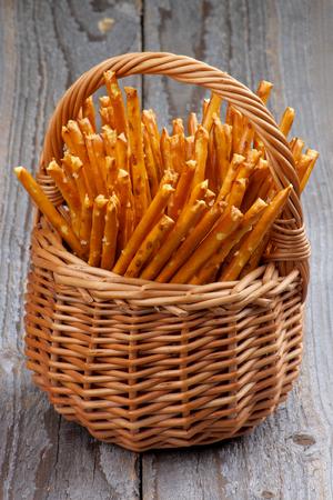 pretzel stick: Bunch of Pretzel Rods Sticks in Wicker Basket isolated on Rustic Wooden background