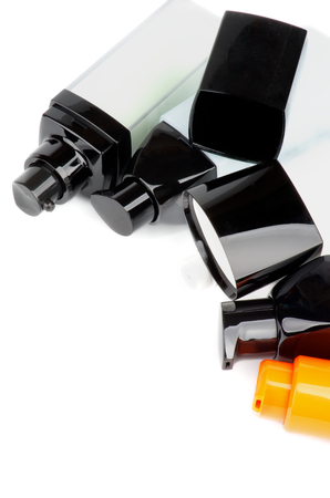 cremas faciales: Marco de Varios faciales cosm�ticos contenedores con limpiador, hidratante y cremas de cuidado aislado en fondo blanco Foto de archivo