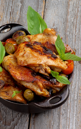 Homemade Roasted Chicken Thighs with Tomatoes, Green Olives and Basil in Black Fry Pan closeup on Rustic Wooden background