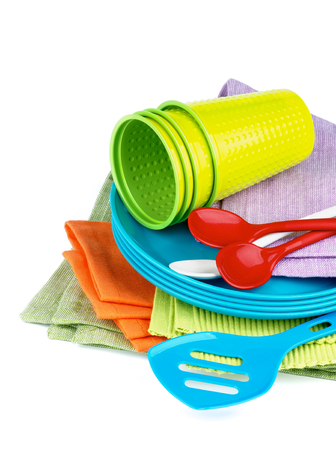 Stack of Multi Colored Cloth Napkins with Plastic Plates, Spoons and Cups isolated on White background photo