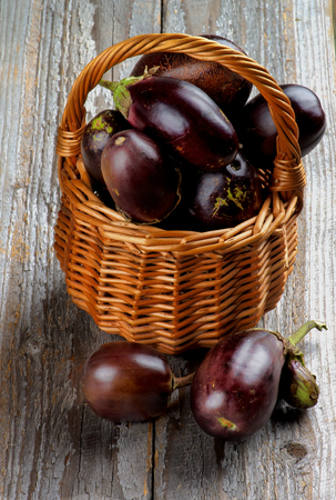 Fresh Ripe Small Eggplants In Wicker Basket on Rustic Wooden background photo