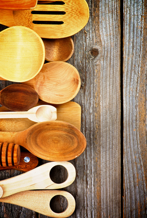 Border of Various Wooden Spoons and Cooking Utensils isolated on Rustic Wooden background photo