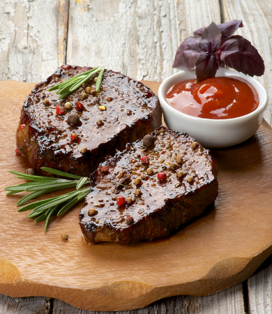 Gourmet Roasted Beef Steaks with Spices, Tomato Sauce and Basil on Wooden Plate on Rustic Wooden background photo