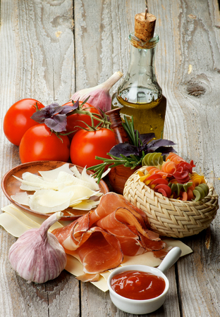 Arrangement of Raw Rotini Pasta, Tomatoes, Spices, Smoked Ham and Olive Oil isolated on Rustic Wooden background photo