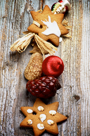 Arrangement of Christmas Ginger Cookies, Red Bauble, Fir Cone and Wooden Decoration In a Row on Rustic Wooden background photo