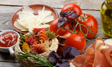 Arrangement of Colorful Raw Rotini Pasta, Smoked Parma Ham, Tomatoes, Grated Cheese, Spices and Olive Oil closeup on Rustic Wooden background photo