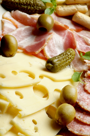 Arrangement Delicious Emmental Cheese with Smoked Meat, Green Olives and Gherkins closeup. Focus on Foreground photo