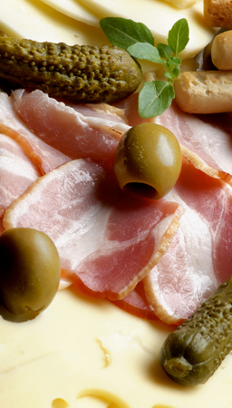 Background of Delicious Smoked Meat, Emmental Cheese, Green Olives and Gherkins closeup. Focus on Sliced Bacon photo