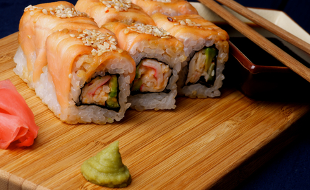chop sticks: Gourmet Salmon Maki Roll with Crab, Cucumber, Sesame Seeds and Soy Sauce, Ginger, Chop Sticks and Wasabi closeup on Straw Mat