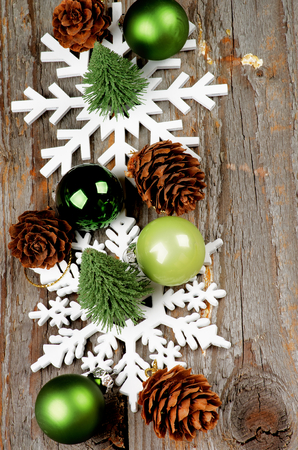 Arrangement of Little Christmas Trees, Green Baubles, Decorative Fir Cones and Snowflake Shapes In a Row on Rustic Wooden background photo