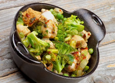 green pea: Homemade Chicken Stew with Broccoli, Bell Pepper and Green Pea in Black Saucepan closeup on Rustic Wooden background