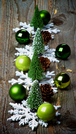 Arrangement of Little Christmas Trees, Green Baubles, Decorative Fir Cones and Snowflake Shapes on Rustic Wooden background photo