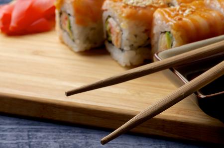 chop sticks: Gourmet Salmon Maki Roll with Crab, Cucumber, Sesame Seeds and Ginger closeup on Straw Mat. Focus on Chop Sticks