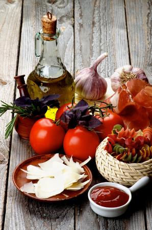 queso rayado: Disposici�n de Raw Rotini Pasta con tomates, especias, jam�n ahumado, aceite de oliva y queso rallado aislado en el fondo de madera r�stica