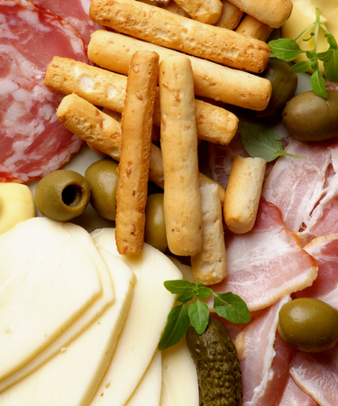 Background of Delicious Smoked Meat and Smoked Salami Salchichon with Bread Sticks, Cheese Sauce, Green Olives , Emmental Cheese and Gherkins closeup photo